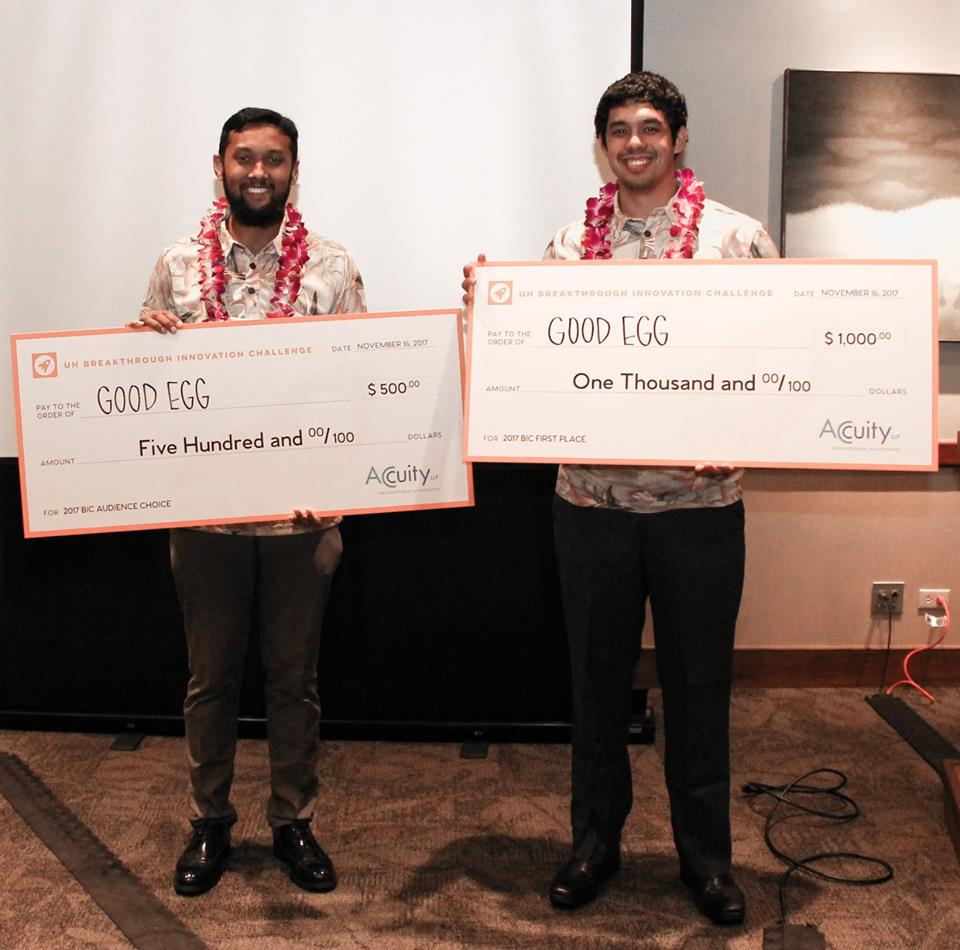 Students Arif Rahman and Kainalu Matthews holding large award checks