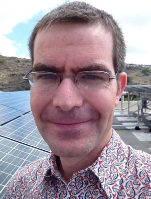 photo, Dr. Matthias Fripp with solar panel test array on roof of Holmes Hall